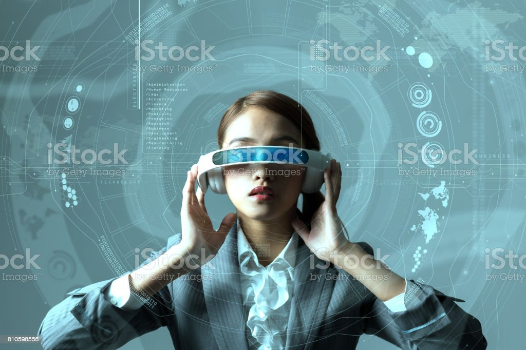 young woman wearing head mount display and futuristic GUI, smart glasses, graphical user interface, heads up display, Internet of Things stock photo