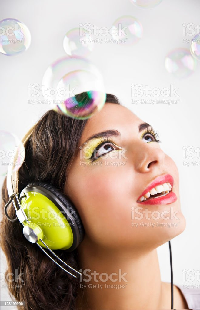 Young Woman Wearing Headphone with Bubbles All Around royalty-free stock photo