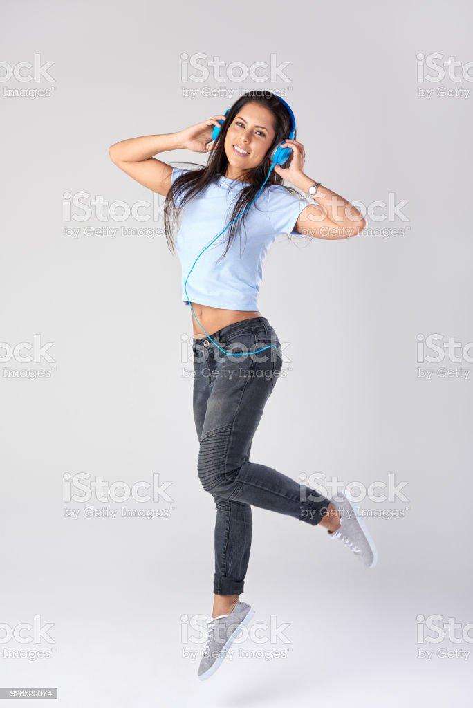 Junge Frau tragen von Kopfhörern und springen – Foto