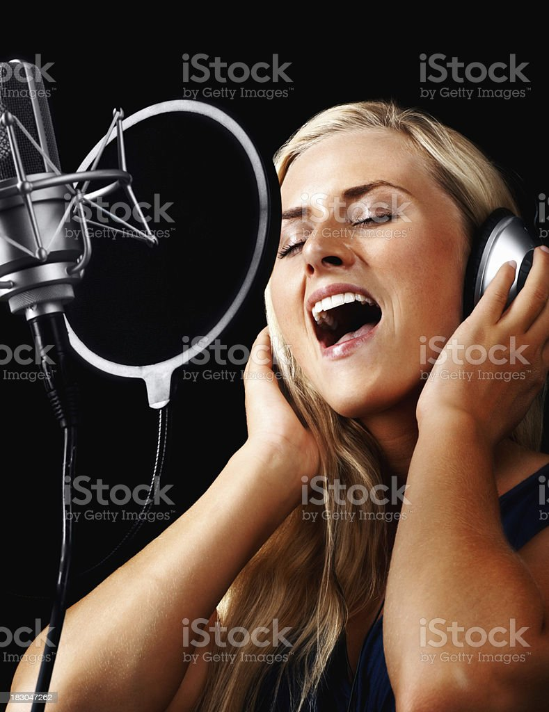 Young woman wearing headphones and singing a song royalty-free stock photo