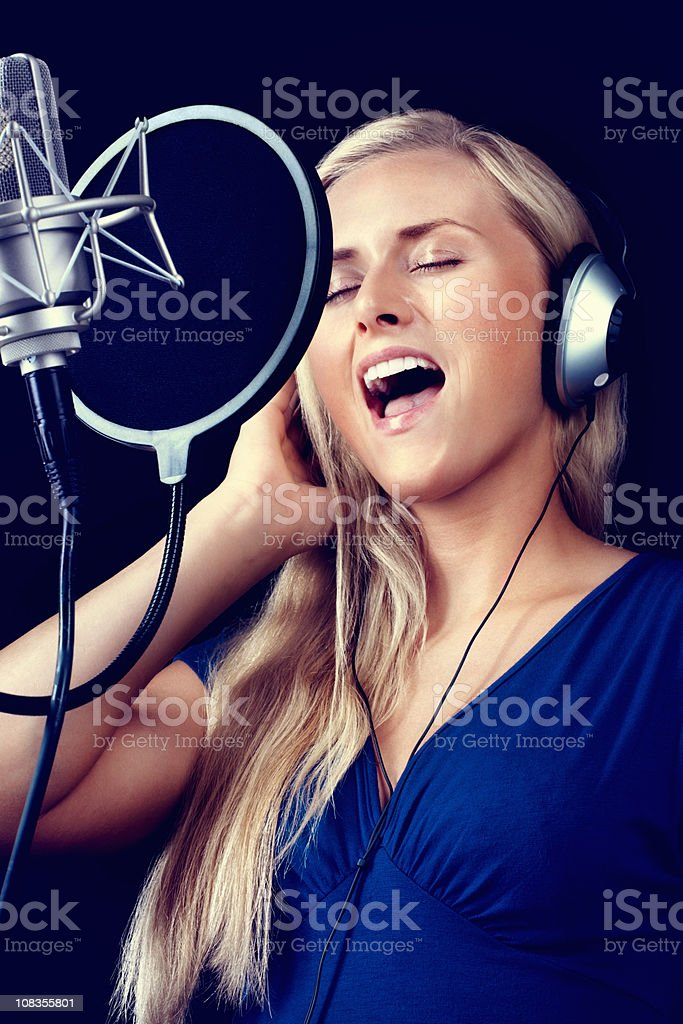 Young woman wearing headphones and singing song with microphone royalty-free stock photo