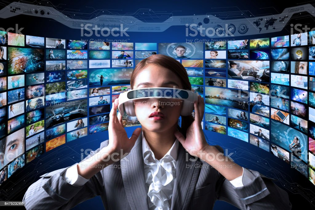 young woman wearing heads mount display and various pictures. internet streaming service concept. stock photo