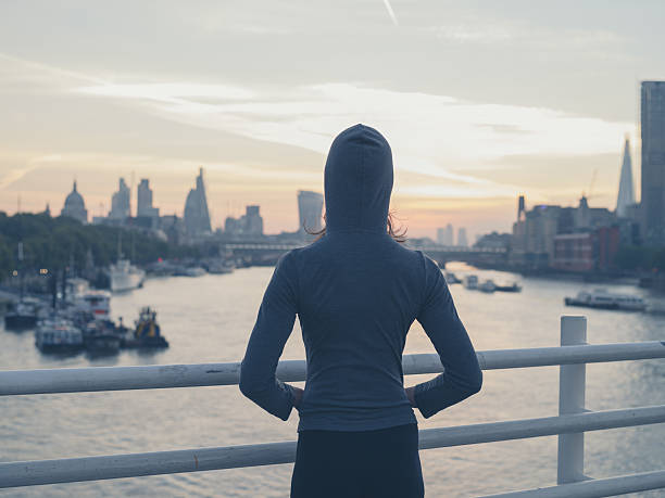 Young woman wearing hoodie on bridge in London at sunrise stock photo