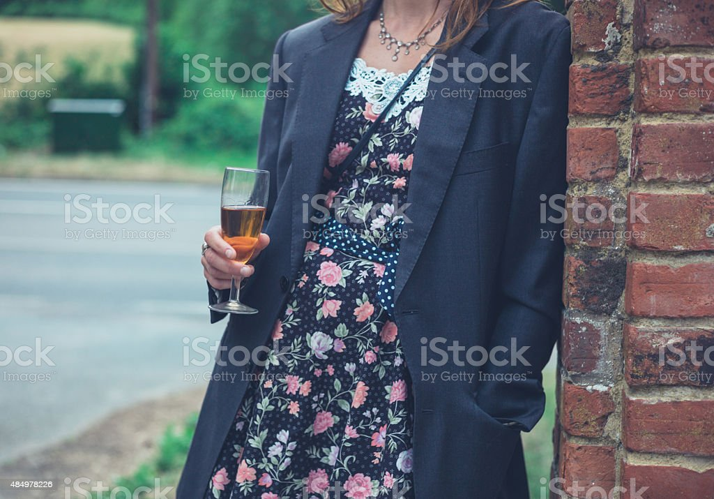 Young woman wearing jacket and drinking wine stock photo