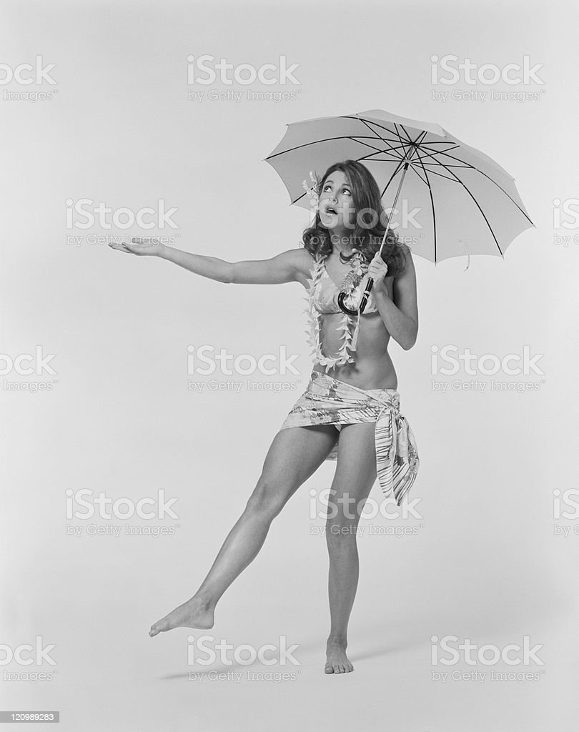 Young woman wearing lei and holding umbrella royalty-free stock photo