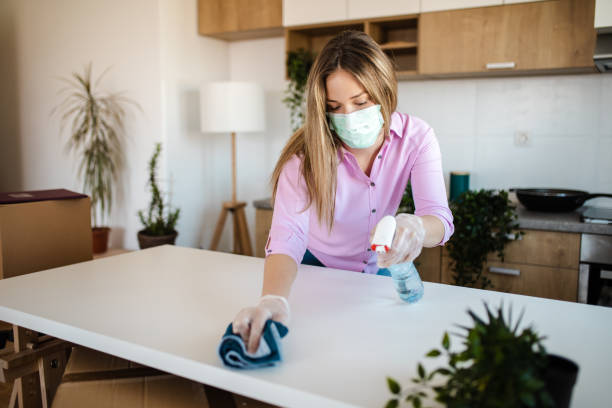 Young woman wearing mask for protection while she cleaning and preparing her house for moving in stock photo