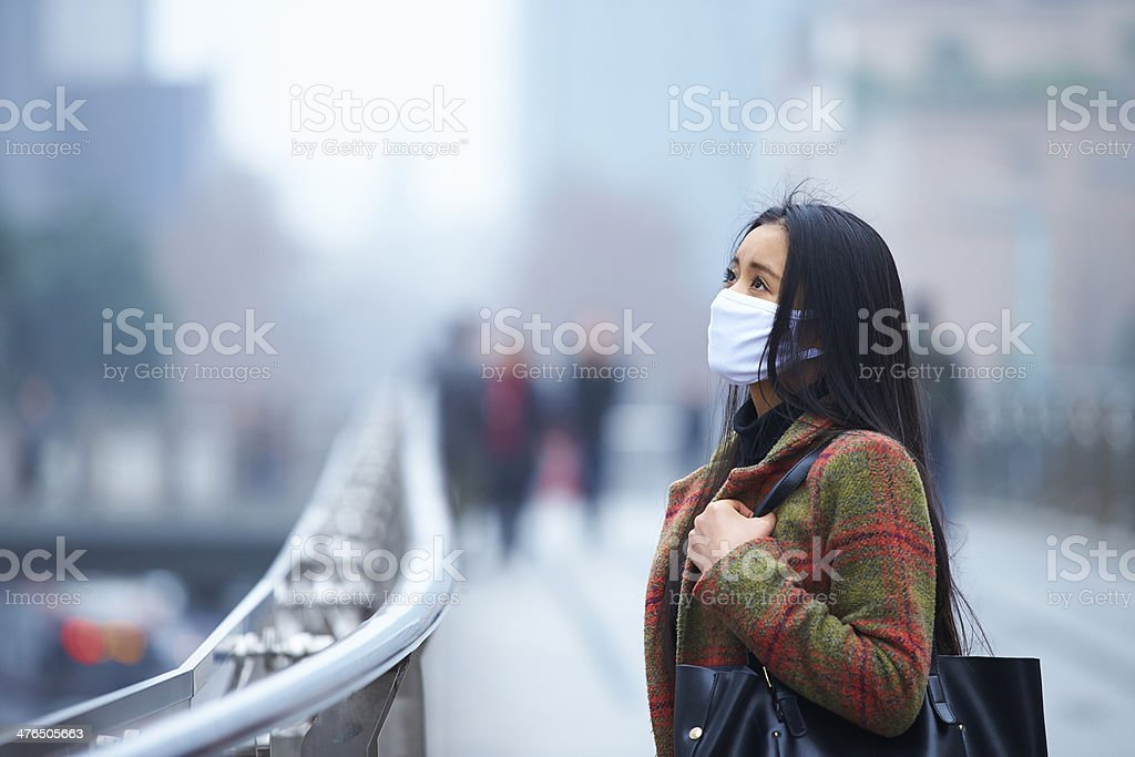young woman wearing mask in the foggy city stock photo