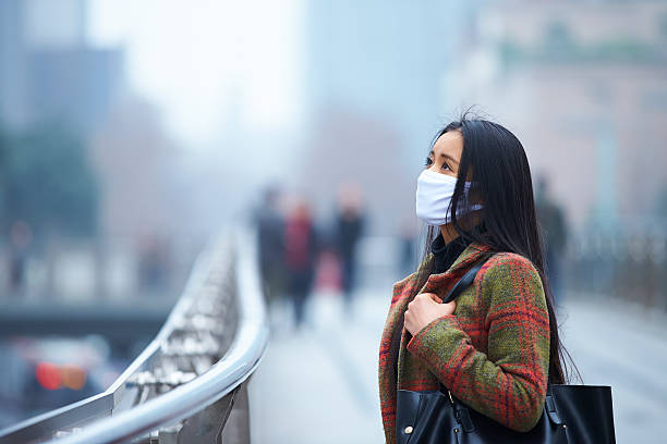 young woman wearing mask in the foggy city - pollution stock pictures, royalty-free photos & images