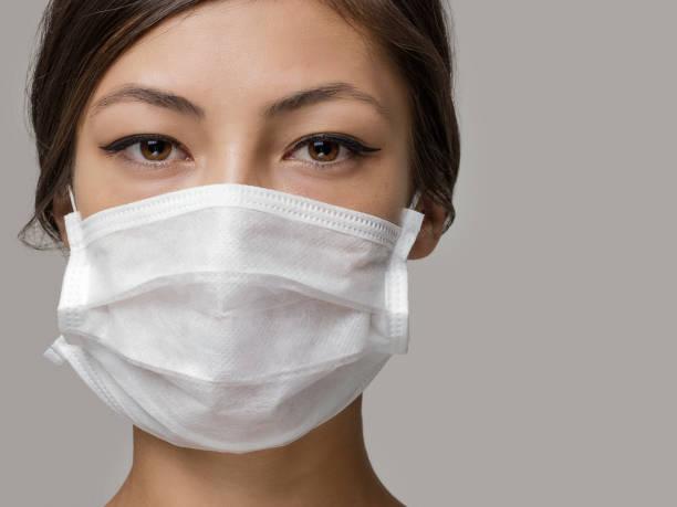 mujer joven con máscara facial médica, retrato de estudio - máscara quirúrgica fotografías e imágenes de stock