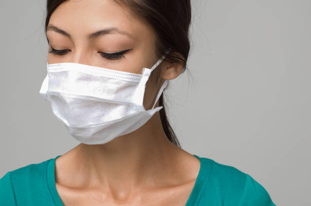 Young woman wearing medical face mask, studio portrait stock photo