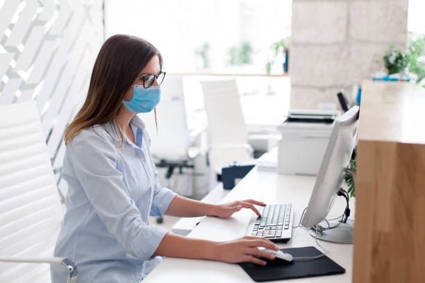 Young woman wearing medical mask in office. Protection employees on workplace. Girl working stock photo