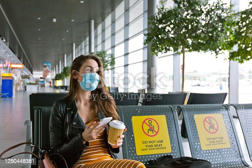 Beautiful young woman traveling by plane during COVID 19, wearing N95 face mask, using a smart phone in airport waiting area.