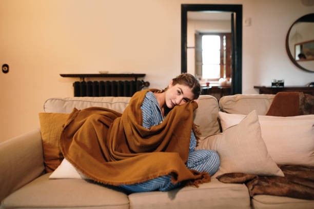 Young woman wearing pajamas and a blanket sitting on sofa stock photo