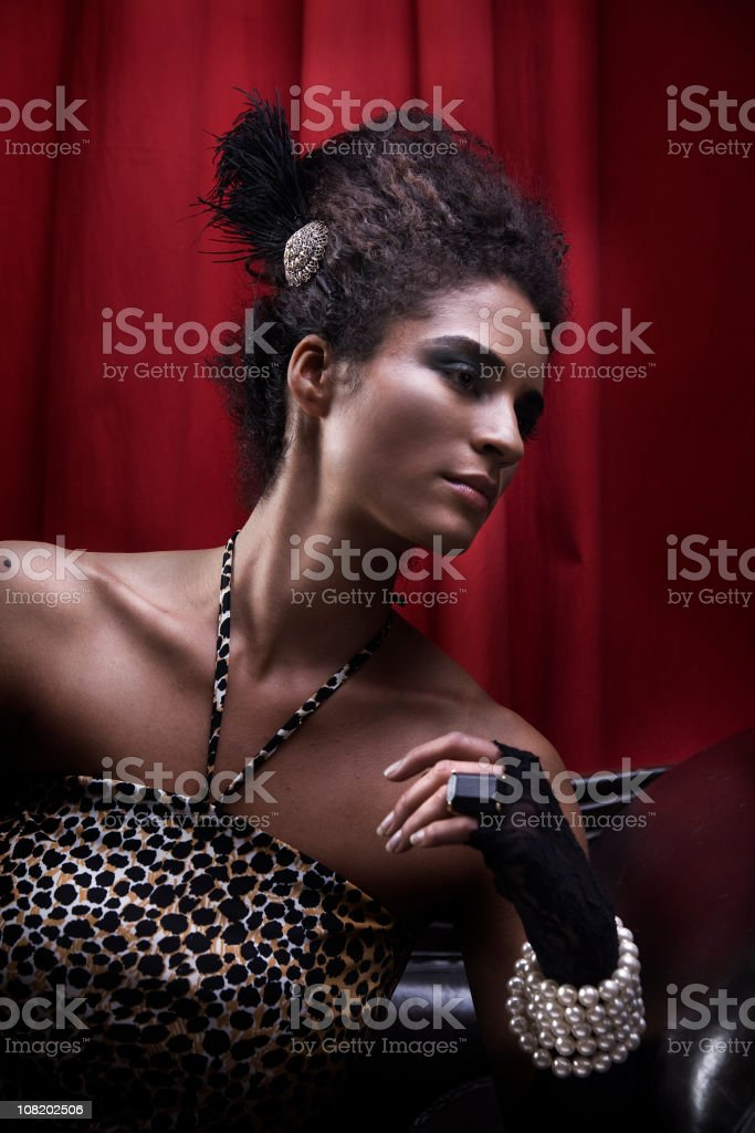 Young Woman Wearing Pearls and Gloves Posing on Red Background stock photo