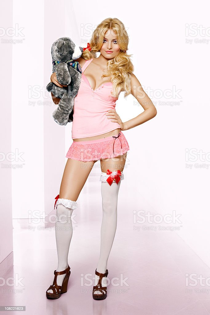 Young Woman Wearing Pink Lingerie and Holding Teddy Bear royalty-free stock photo