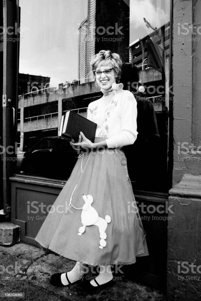 Young Woman Wearing Poodle Skirt and Holding Books stock photo
