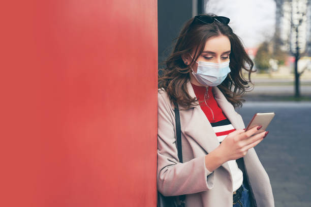 Young woman wearing protection face mask against coronavirus COVID-19 aka 2019-nCoV is looking for information about the outbreak on hwe smartphone while standing on the street. Concept of coronavirus quarantine and pandemic. stock photo