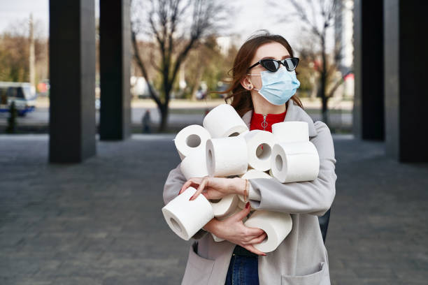 Young woman wearing protection face mask and sunglasses against coronavirus MERS-Cov, Novel coronavirus 2019-nCoV holds many rolls of toilet paper on the city street. Concept of coronavirus quarantine and pandemic. stock photo