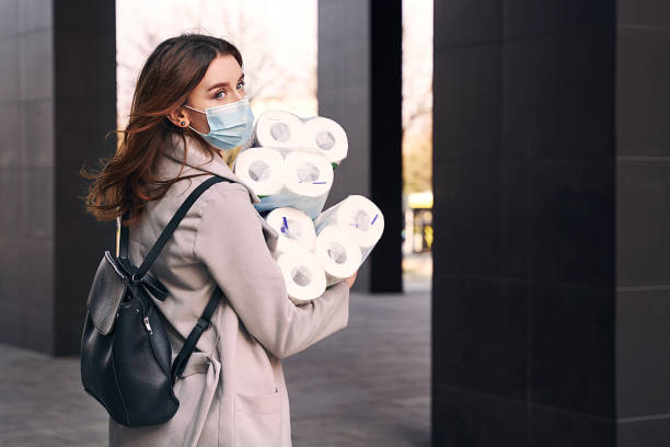 Young woman wearing protection face mask and sunglasses against coronavirus COVID-19 holds many bundles of toilet paper rolls on the city street. Concept of coronavirus quarantine and pandemic. stock photo