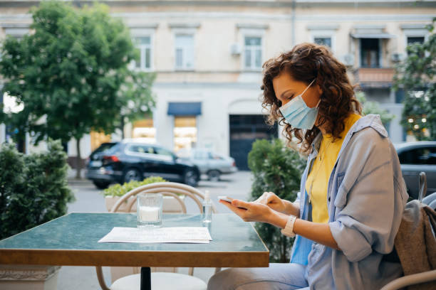 Young woman wearing protective face mask disinfects her hands and her mobile phone stock photo