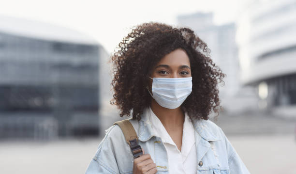 Young woman wearing protective face mask in a city stock photo