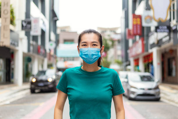 Young woman wearing protective face mask in city for protection from cold and flu and viruses. Young woman wearing protective face mask in city street due to the polluted air one mid adult woman only stock pictures, royalty-free photos & images
