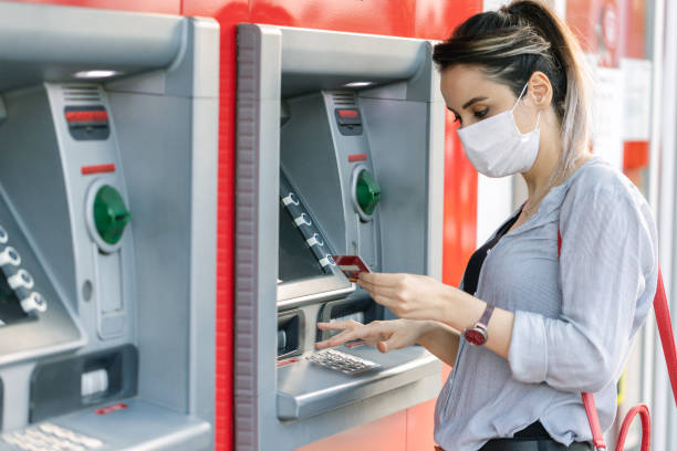 Young woman wearing protective face  mask while withdrawing money at ATM Young woman wearing protective face mask while withdrawing money at ATM banks and atms stock pictures, royalty-free photos & images