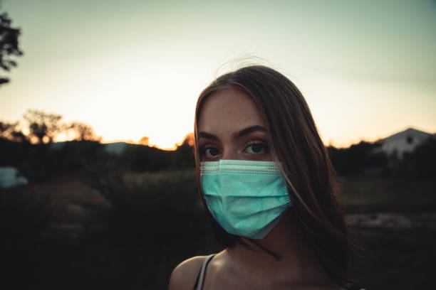 Young woman wearing protective facemask feeling sick stock photo