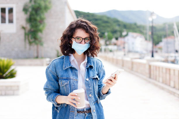 Young woman wearing protective mask at town street. Life post-quarantine. Girl walking alone outdoor stock photo