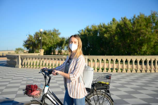 Junge Frau trägt Schutzmaske mit E-Bike am Meer – Foto