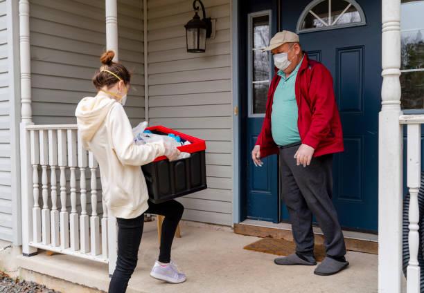 Junge Frau trägt Schützenschutz n95 Maske, ein Kurier, liefert die Lebensmittel verpackt in den wiederverwendbaren Plastikbehälter an einen Kunden, ein Senior Mann, während COVID-19 Ausbruch verpackt. – Foto