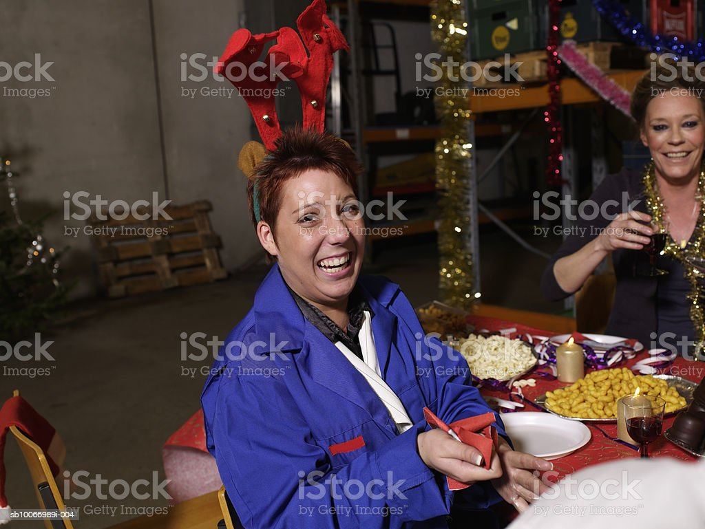 Young woman wearing protective overalls and reindeer antlers laughing at charismas table in warehouse, portrait royalty free stockfoto