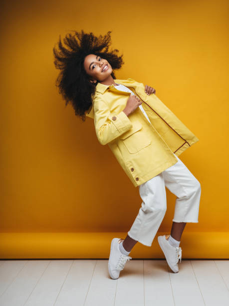 young woman wearing raincoat - pics for cool girl stock pictures, royalty-free photos & images
