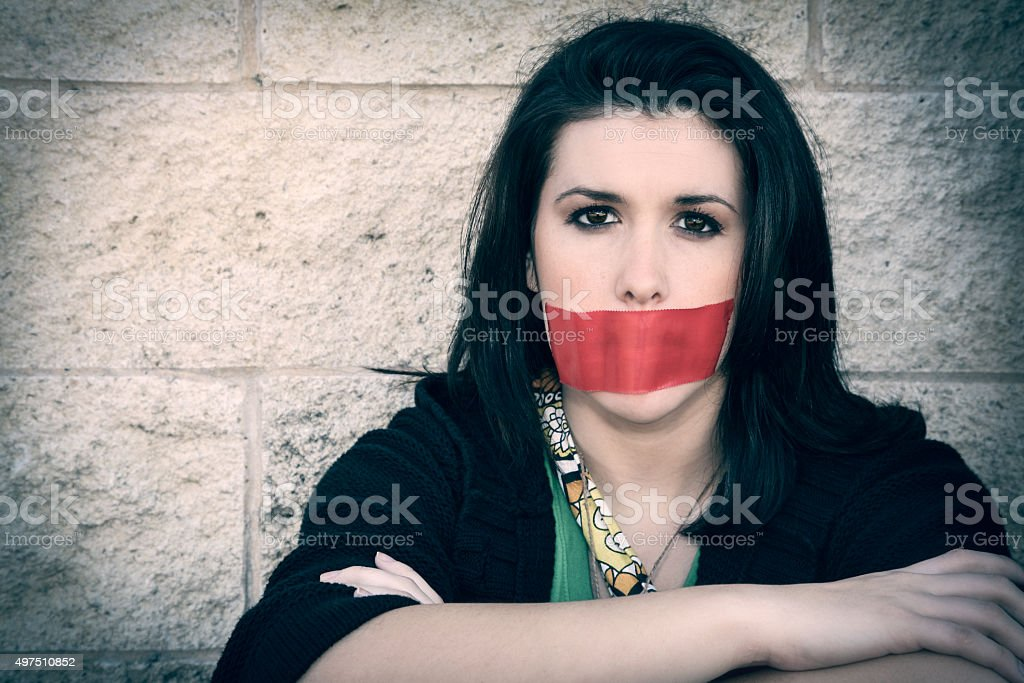 Young woman wearing red tape over mouth in protest stock photo