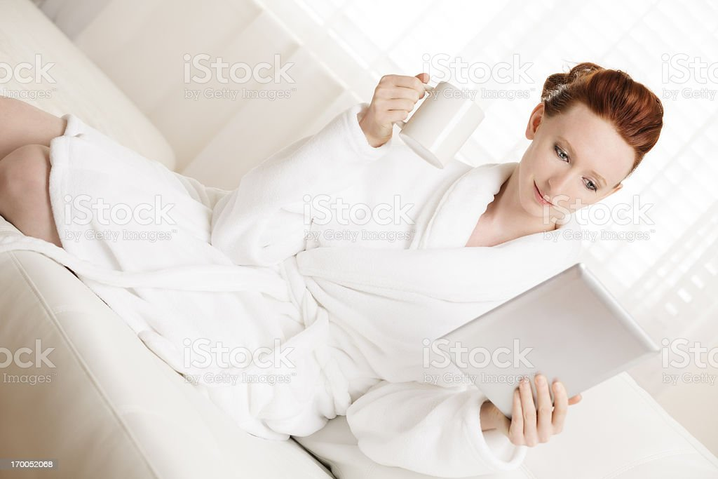 Young woman wearing robe reading something on digital tablet royalty-free stock photo