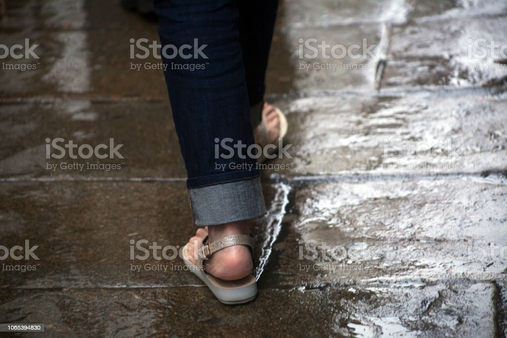 ba732afeabff Young woman wearing sandals walking on wet street paving stone floor.  royalty-free stock
