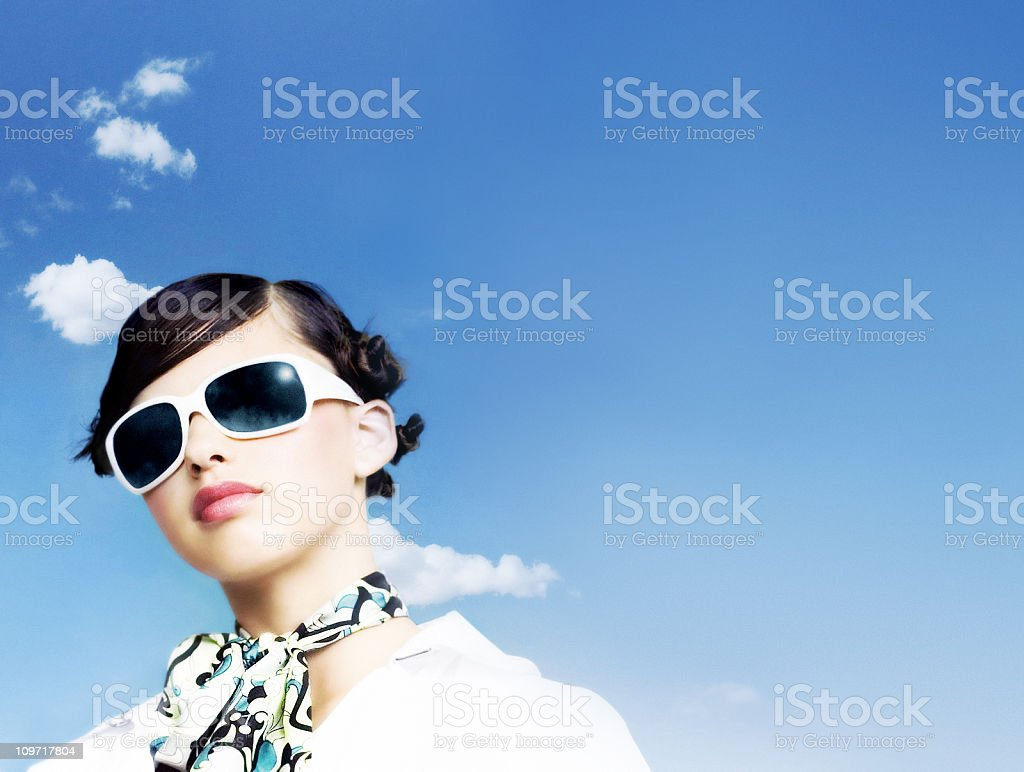 Young Woman Wearing Scarf and Sunglasses Against Blue Sky royalty-free stock photo