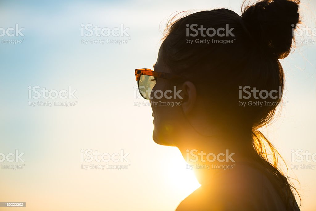 Young woman  wearing sunglasses looking at sunset stock photo
