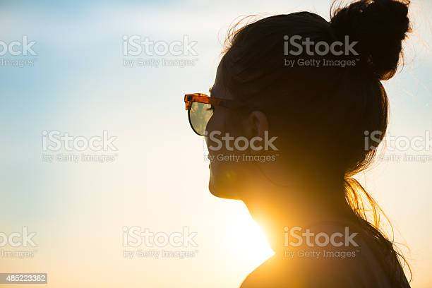 Photo of Young woman  wearing sunglasses looking at sunset