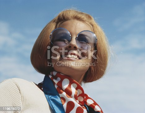 istock Young woman wearing sunglasses, smiling, close-up 119679072