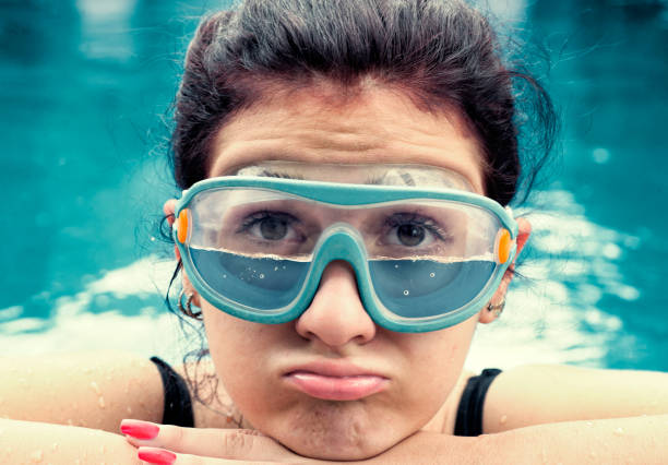 young woman wearing swimming glasses half filled - frowning stock photos and pictures