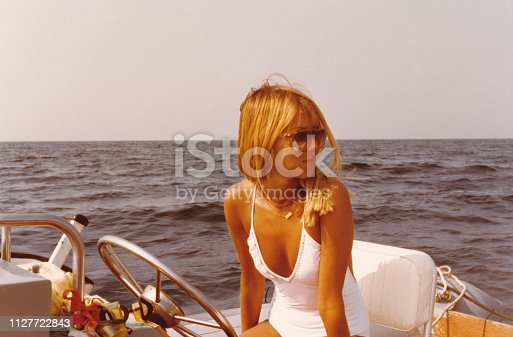 Young beautiful woman on a dinghy in 1970