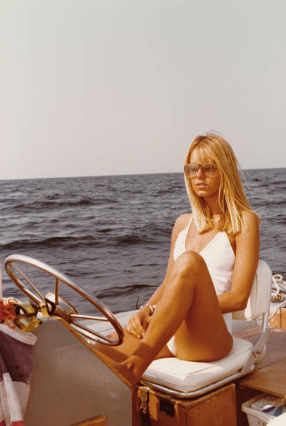 Young woman wearing swimwear on a dinghy in 1970 Young beautiful woman on a dinghy in 1970 sailing dinghy stock pictures, royalty-free photos & images