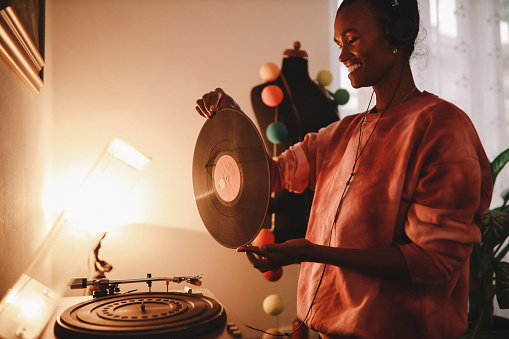 Young woman wearing tie dye shirt playing her record collection at home