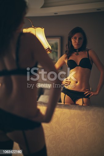 Beautiful young woman looking at herself in mirror. She wears black underwear and looks very sensual and attractive