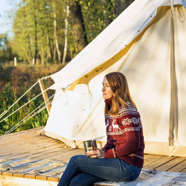 Young woman wearing warm jersey drinking cofee while sitting near a camping tent stock photo