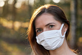 Young woman wearing white cotton virus mouth nose mask, blurred sunset lit trees in background, closeup face portrait