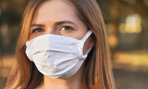 Young woman wearing white cotton virus mouth nose mask, nice bokeh in background, closeup face portrait stock photo