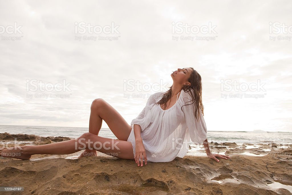 Young woman wearing white top sitting on sand, portrait stock photo