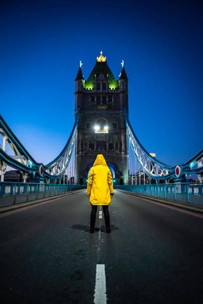 Young woman, wearing yellow rain coat on Tower Bridge stock photo